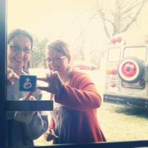 Dana Bennett and Michelle Johnson-Howell place the International Breastfeeding Logo on the doors of local businesses.